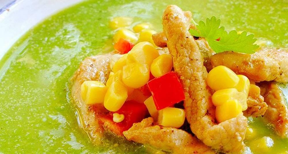 Grønn suppe med topping av svinekjøtt, paprika og mais