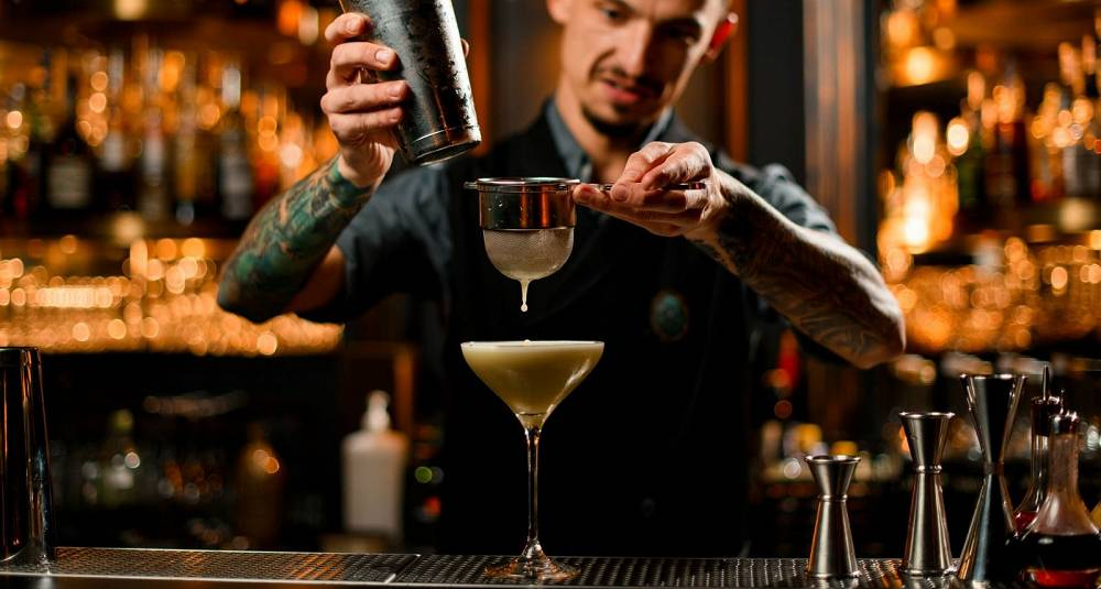 professional-bartender-pouring-yellow-creamy-alcoholic-drink-from-the-picture-id1197154503.jpg